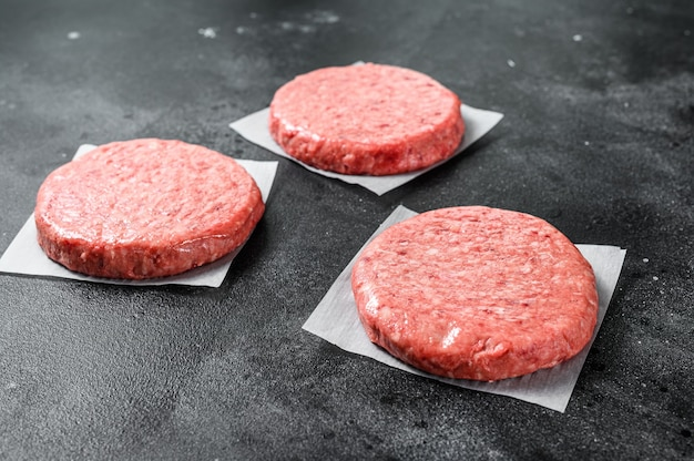 Raw ground meat cutlet, mince beef. burger patties. black background. top view.