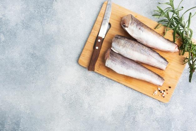 Туша сырой рыбы хек на деревянной разделочной доске