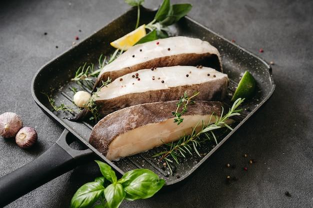 그릴 팬에서 요리를 위해 준비된 허브와 레몬을 곁들인 생 넙치 생선 스테이크. 두뇌와 정신 맑음에 좋은 건강한 오메가 3 불포화 지방 공급원