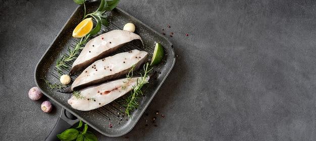 그릴 팬에서 요리를 위해 준비된 허브와 레몬을 곁들인 생 넙치 생선 스테이크. 복사 공간이 있는 긴 배너입니다. 두뇌와 정신의 선명도에 좋은 건강한 오메가 3 불포화 지방