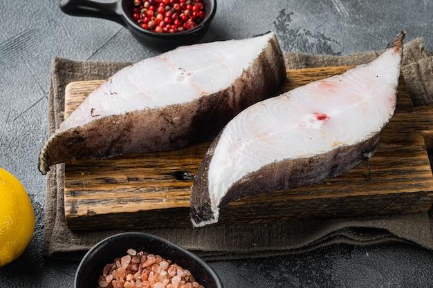 灰色の石のテーブルの背景に、食材とローズマリーハーブを含む生のオヒョウ海水魚ステーキセット