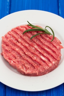 Raw hamburger on white plate on wooden surface