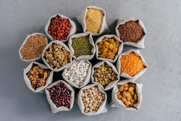 날것의 건강한 곡물 음식과 콩과 식물. 곡물과 말린 과일의 헤센 가방.