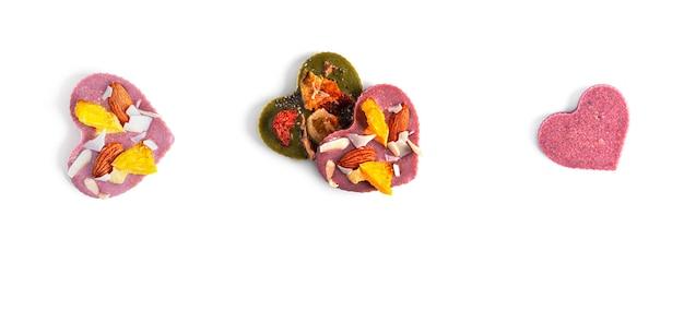 원시 심장 모양의 말린 과일과 견과류는 흰색 바탕에 초콜릿. 고품질 사진