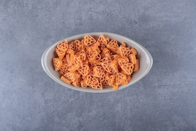 Сырые макароны в форме сердца в керамической миске.
