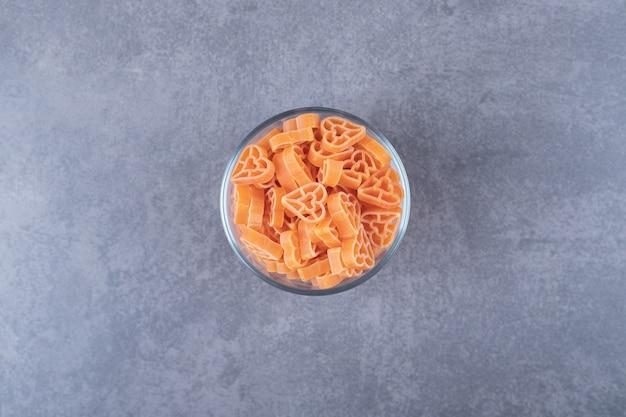 Сырые макаронные изделия в форме сердца в стеклянной миске.