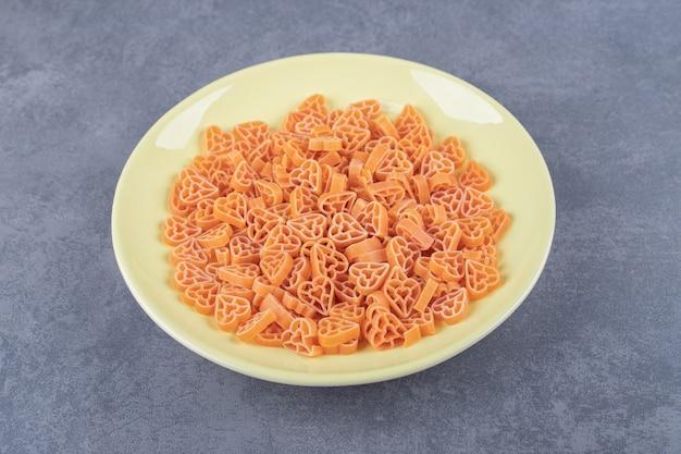 Сырые макароны в форме сердца на желтой тарелке.