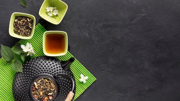 Сырой ингредиент травяного чая с чайником на зеленом коврике на черной поверхности