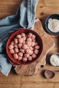 Сырые домашние итальянские традиционные фрикадельки с пармезаном и хлебом