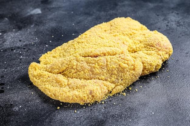生の自家製パン粉をまぶしたドイツのワイナーシュニッツェル。黒の背景。上面図。