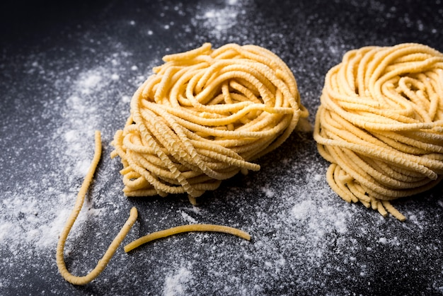 Raw homemade capellini pasta nest with flour on a black background