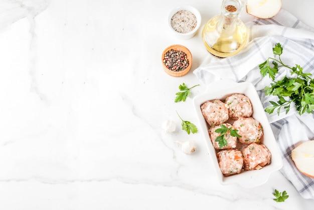Сырые домашние куриные или индейки фрикадельки в выпечки на белом фоне мрамора. копировать пространство