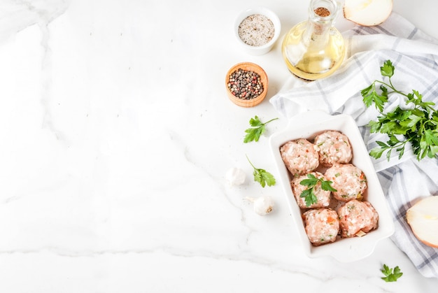 Raw homemade chicken or turkey meatballs in baking dish on white marble background. copy space.