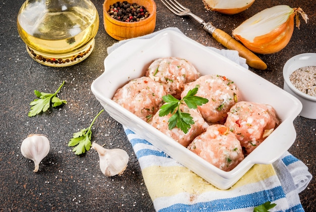 Raw homemade chicken or turkey meatballs in baking dish