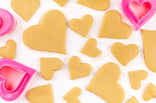 Raw homemade heart shaped cookies with pink cookie cutter and flour