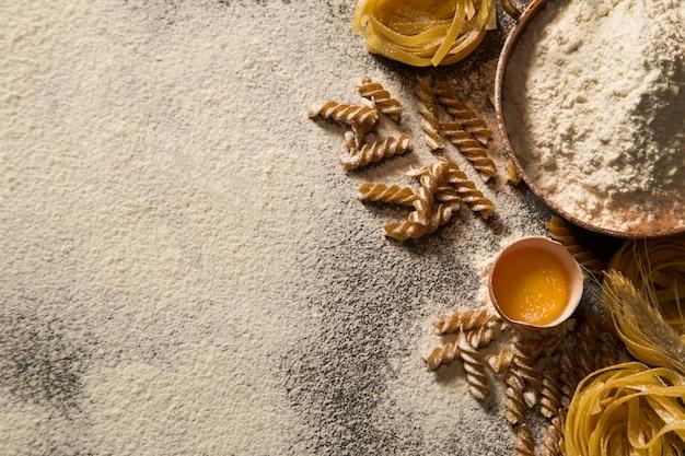 Сырые домашние макароны и ингредиенты для макарон на деревянном столе