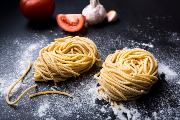 Raw homemade pasta nest on flour with garlic and tomato at background