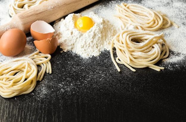 Сырые домашние макароны с ингредиентами на черном фоне. выборочный фокус.