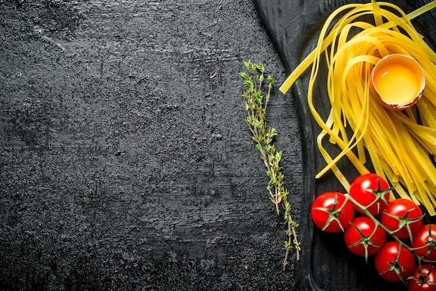 Сырые домашние макароны с тимьяном, яйцом и помидорами. на черном деревенском фоне