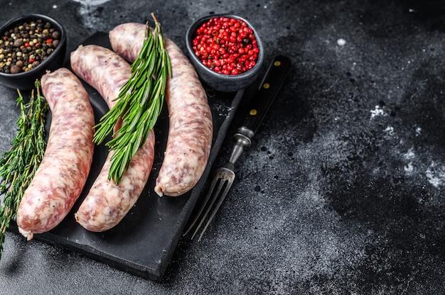 Сырые домашние колбаски из свинины в кожуре с зеленью
