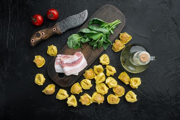 검은 테이블에 나무 커팅 보드에 경화 햄 세트가있는 원시 수제 tortellini, 평면도 평면 누워