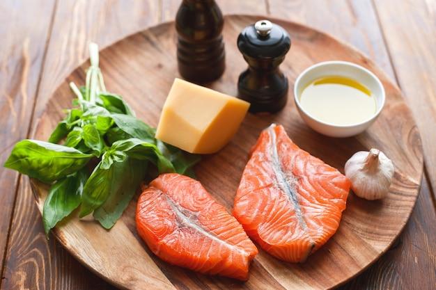 ビューの上に生のハンプバックサーモンステーキ、チーズ、素朴な木製の背景。おいしい料理とフライパンのための新鮮な食材を使ったフィレ。上面図。健康とダイエット食品のコンセプト。
