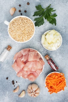 Raw ingredients for cooking pilaf, brown rice and chicken fillet, grated carrots and chopped onions, pepper tomato garlic herbs and spices. gray, top view.