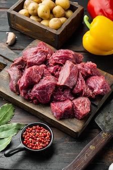 Сырье для гуляша. свежая сырая нарезанная говядина со сладким перцем и картофелем на старом темном деревянном столе