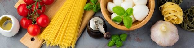 회색 콘크리트 배경에 이탈리아 파스타, 스파게티, 탈리아텔레, 푸실리, 마늘, 바질, 모짜렐라, 상추, 후추, 체리 토마토, 올리브 오일을 준비하기 위한 원료. 평면도