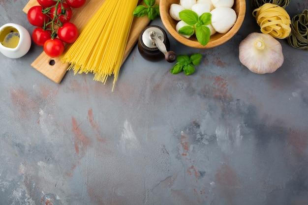Сырье для приготовления итальянской пасты, спагетти, тальятелле, фузилли, чеснока, базилика, моцареллы, салата, перца, помидоров черри и оливкового масла на сером бетонном столе. вид сверху