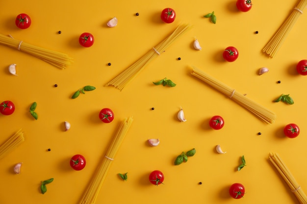 Raw ingredients for making pasta. spaghetti, tomatoes, garlic and basil leaves. herbs and spices for italian food. meal preparation. yellow background. cooking homemade delicious cuisine. eating