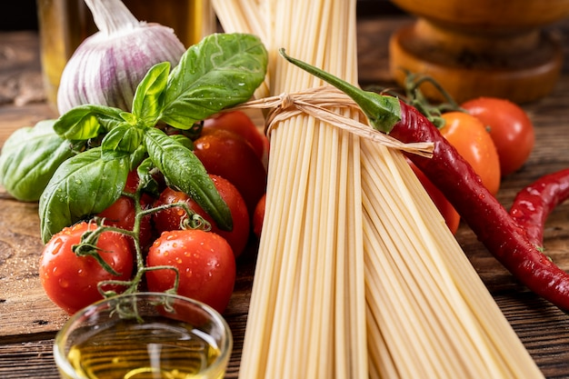 Raw ingredients pasta spaghetti on old rustic wooden background