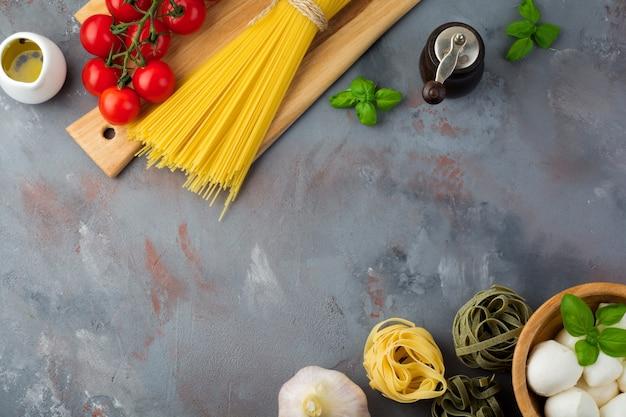 Raw ingredients for the preparation of italian pasta, spaghetti, tagliatelle, fusilli, garlic, basil, mozzarella, lettuce, pepper, cherry tomatoes and olive oil on a gray concrete table. top view