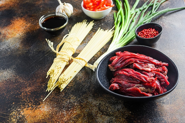 Raw ingredients for stir fry chinese noodles with vegetables and beef in black bow