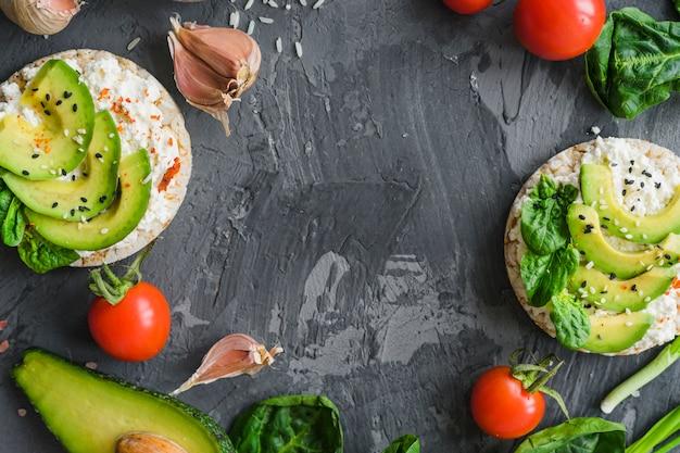 Materie prime con avocado; crema di formaggio e torta di riso su sfondo con texture