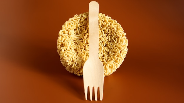 木製の使い捨てフォークが付いた円形の生即席めん。パスタ、沸騰したお湯を注いで数分待つだけで十分です。スパゲッティ。スペースをコピーします。