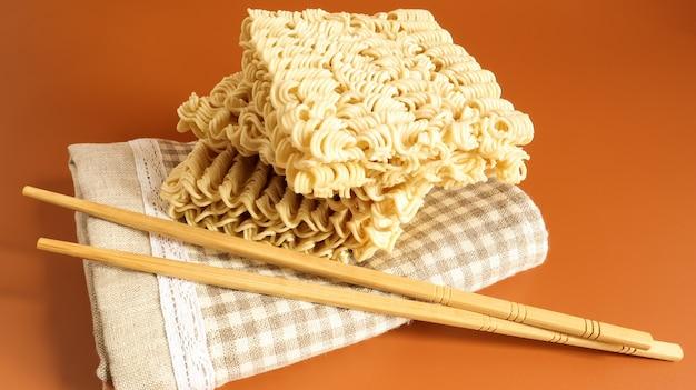 黄色の背景に箸でタオルの上に生のインスタントラーメン。パスタ、その上に沸騰したお湯を注いで数分待つだけで十分です。スペースをコピーします。