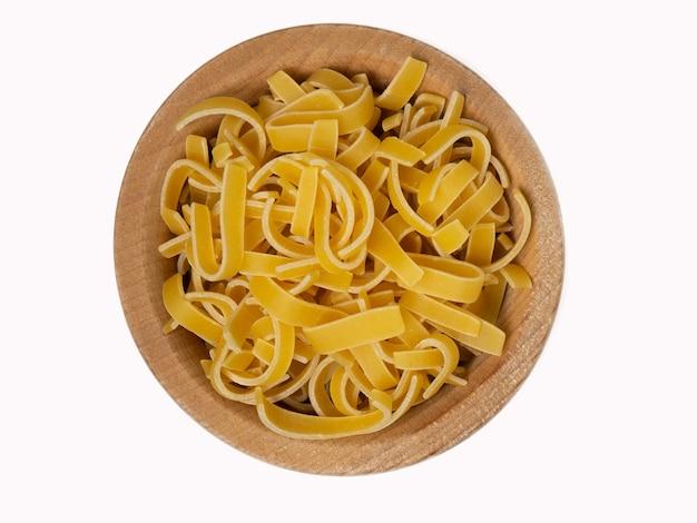 흰색 배경에 고립 된 나무 그릇에 원시 이탈리아 파스타, 상위 뷰