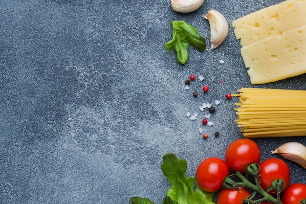 Raw italian pasta spaghetti and cooking ingredients cherry tomatoes cheese greens. italian food dark stone surface. top view with copy space