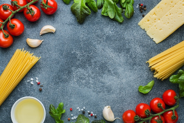Raw italian pasta spaghetti and cooking ingredients cherry tomatoes cheese greens
