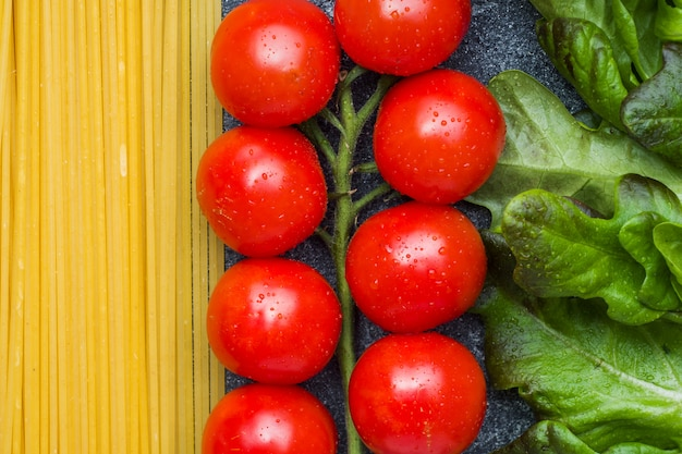 Raw italian pasta spaghetti and cooking ingredients cherry tomatoes greens