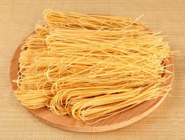 Raw italian pasta on wooden tray