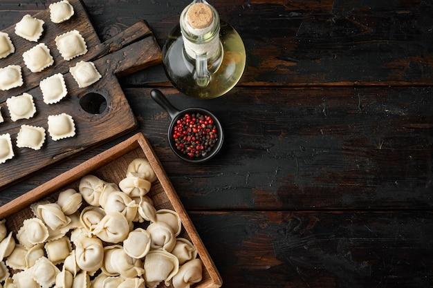 신선한 파마산 치즈와 바질을 곁들인 생 이탈리아 라비올리 토르텔리니, 오래된 어두운 나무 테이블 배경에 놓인 토마토, 카피스페이스와 텍스트 공간이 있는 평면도