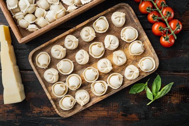 신선한 파르메산 치즈와 바질을 곁들인 생 이탈리아 라비올리 토르텔리니, 오래된 어두운 나무 테이블 배경에 놓인 토마토, 평면도