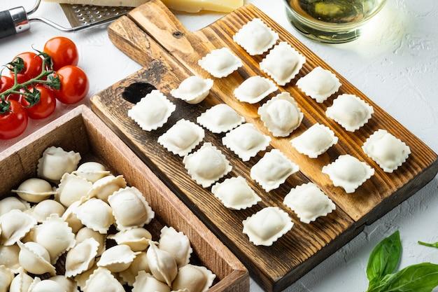 신선한 파르메산 치즈와 바질을 곁들인 생 이탈리아 라비올리 토르텔리니, 흰색 배경에 나무 판자 위에 놓인 토마토
