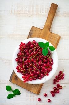 赤スグリとミントの葉の生のジューシーで新鮮なベリーを白いプレートに。