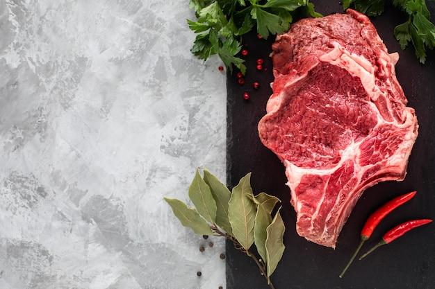 黒いスレートボードで焼く準備ができてジューシーな生肉ステーキ。骨のステーキ、チェリートマト、トウガラシ、ハーブの入った木製のまな板の上で仔牛テキスト用のスペース。上面図