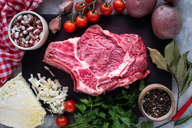 生のジューシーな肉のステーキは、黒いスレート板で焼く準備ができています。骨付きステーキ、木製のまな板で子牛肉、チェリートマト、唐辛子、小豆、ハーブ。スープの材料。上面図