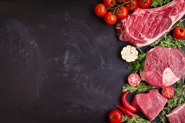 검은 분필 보드 배경에 구이에 대 한 준비가 원시 육즙 고기 스테이크.