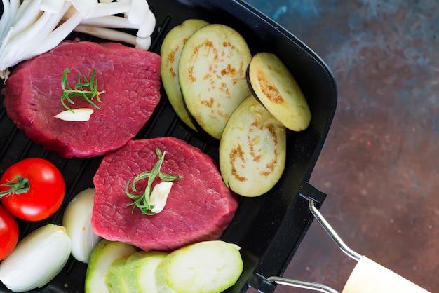 Сырцовые сочные стейки в лотке готовом для жарить на деревенском бетоне. стейки из свежей говядины с зеленью, чесноком, перцем, солью и помидорами.